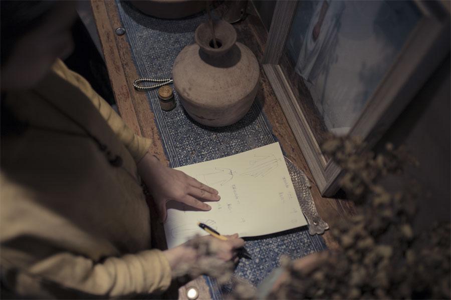 王玭根据客户要求,当场构画衣服草图。