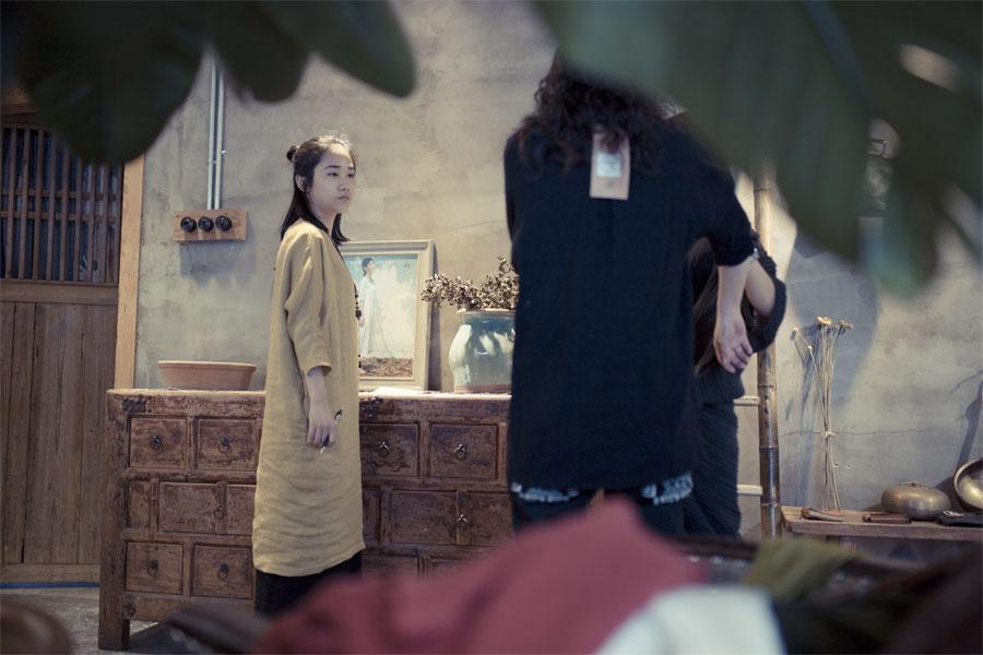 在工作室内,有两名顾客上门,王玭与他们交流衣服订制的细节。