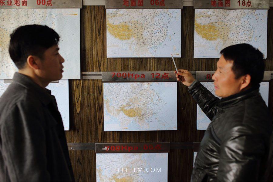 气象预报员朱靖国正在向王亚林介绍近期气象云图运动情况。